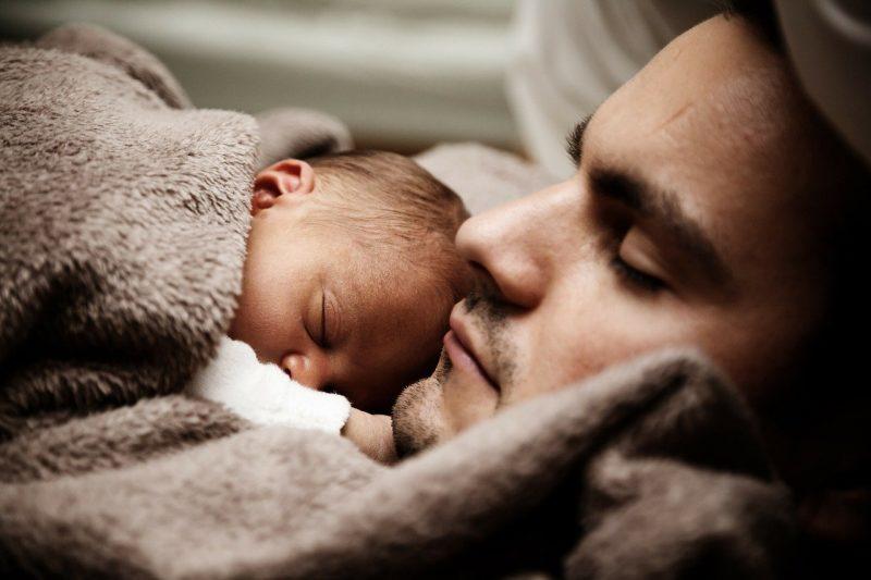 slapende baby bij vader
